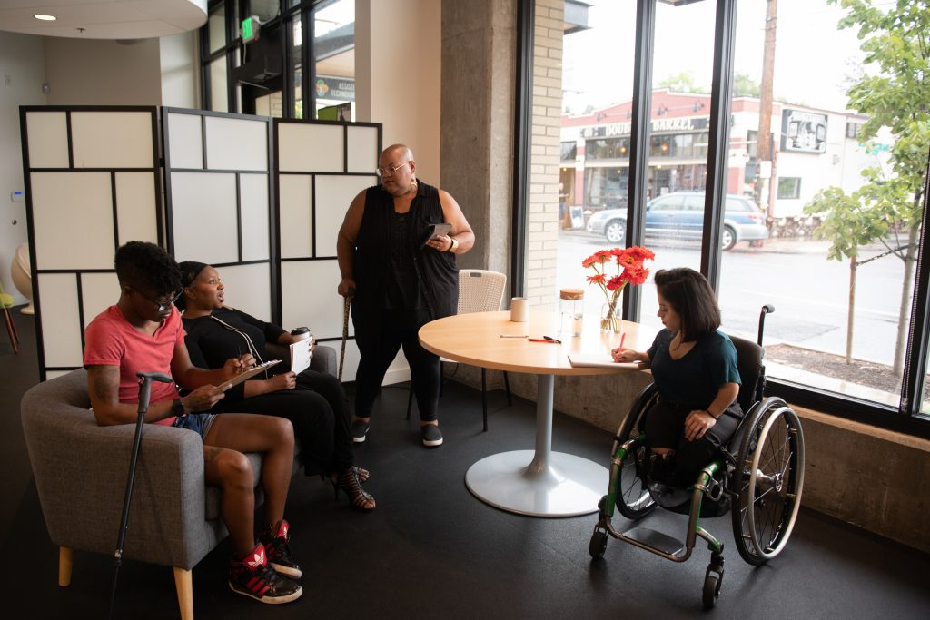 Four disabled people of color face each other in a open circle during a meeting. Two Black people sit on a couch with a cane leaning off the side while a Black non-binary person stands with a tablet and cane. A South Asian person in a wheelchair takes notes.
